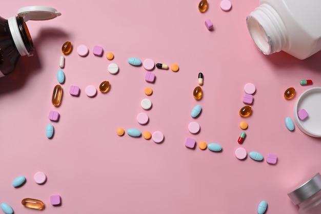 Różne tabletki leku na różowym tle.
