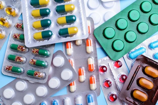 Różne tabletki, tabletki w blistrach foliowych, leki leki na niebieskim tle