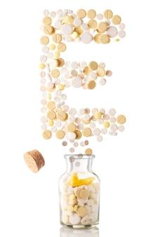 Różne tabletki wylatują ze szklanego słoika w formie litery e, na białym tle