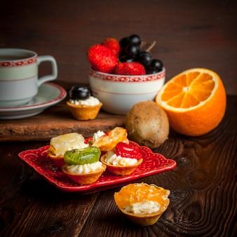 Różne tartaletki z filiżanką herbaty i półmisek owoców i pomarańczą w talerzu