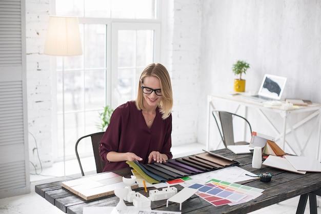 Różne tkaniny. widok z góry na wesołą projektantkę wpatrującą się w dół i wybierając tapicerkę