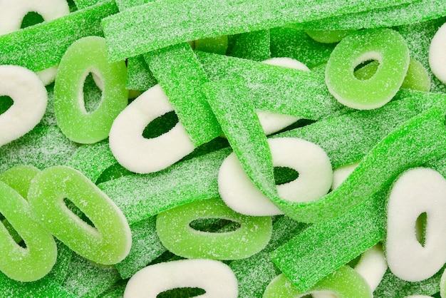 Różne tło zielone żelki cukierki. widok z góry. galaretki.