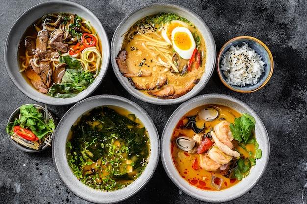 Różne tradycyjne azjatyckie zupy. miso, ramen, tom yam, pho bo. czarne tło. widok z góry