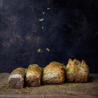 Różne tureckie baklawy z mielonymi pistacjami w drewnianej płytce