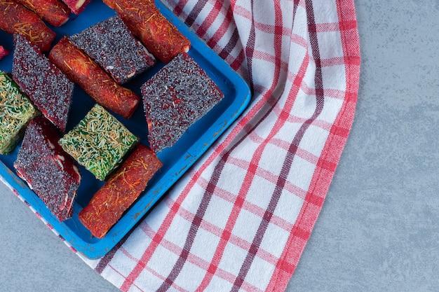 Różne tureckie smaki rozkoszy na drewnianej desce, na ściereczce, na marmurowym stole.