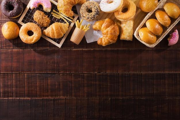 Różne typy fast foodów na drewnianym stole z widokiem z góry z miejscem na kopię.