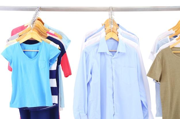 Różne ubrania na wieszakach, na szarej powierzchni
