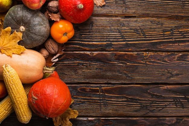 Różne warzywa, dynie, jabłka, gruszki, orzechy, pomidory, kukurydza, suche żółte liście na drewniane tła. jesienny nastrój, lato. żniwa
