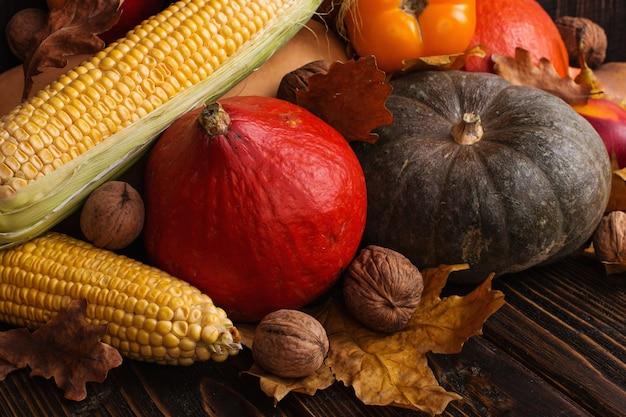 Różne warzywa, dynie, jabłka, gruszki, orzechy, pomidory, kukurydza, suche żółte liście na drewniane tła. jesienny nastrój, leżał płasko. żniwa