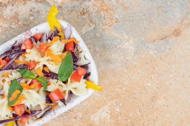 Różne warzywa i farfalle w misce na marmurowej powierzchni