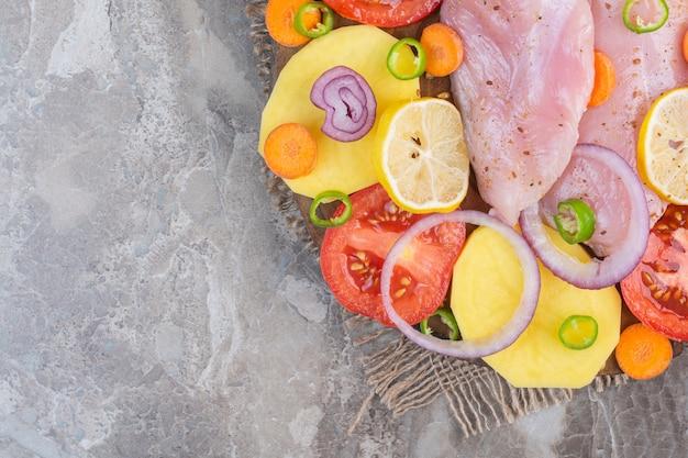 Różne warzywa i piersi z kurczaka, na marmurowym tle.