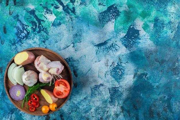 Różne warzywa i podudzie z kurczaka na drewnianym talerzu, na niebieskim tle.