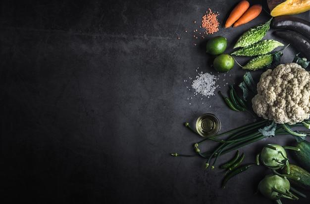 Różne warzywa na czarnym stole z miejscem na wiadomość do pisania