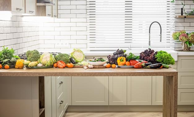 Różne warzywa na drewnianym stole na tle wnętrza nowoczesnej kuchni.