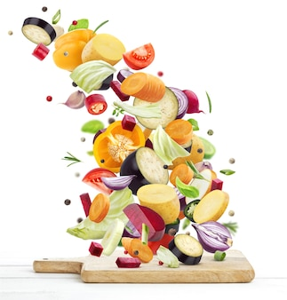 Różne warzywa spadające na drewnianą deskę do krojenia na białym tle