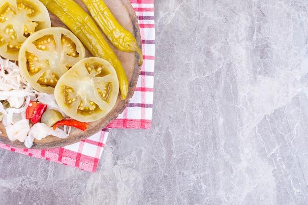 Różne warzywa w puszkach na desce na ręczniku, na marmurze.