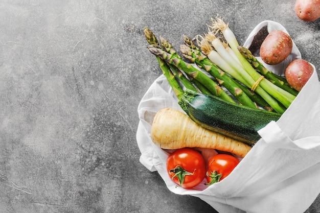 Różne warzywa w woreczku tekstylnym na szaro