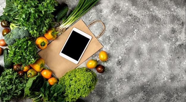 Różne warzywa z komputerem typu tablet i papierową torbą na zakupy. widok z góry transparent z miejscem na tekst.