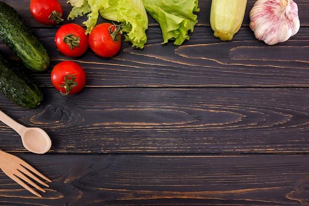 Różne warzywa, zioła, drewnianą łyżką i widelcem na drewnianym tle. skopiuj miejsce. miejsce na twój tekst. leżał płasko.