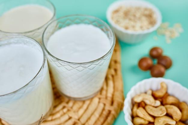 Różne wegańskie mleko i składniki roślinne, mleko bez mleka, alternatywne rodzaje wegańskich mlek w szklankach na niebieskim tle z miejscem na kopię