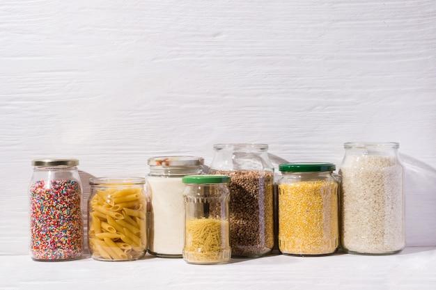 Różne zboża, makarony i cukierki w szklanych słoikach. koncepcja przechowywania zero odpadów. przechowywanie żywności w kuchni przy niskim poziomie odpadów