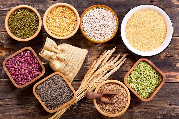 Różne zboża, nasiona, fasola i ziarna na drewnianym stole, widok z góry