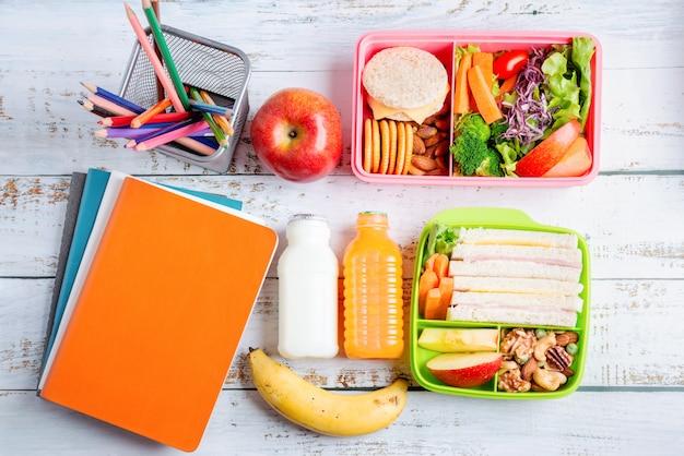 Różne zdrowe pudełka na kanapki. dziecięce opakowanie bento do zestawu szkolnego w plastikowym opakowaniu, banana i jabłka z sokiem pomarańczowym, mlekiem.