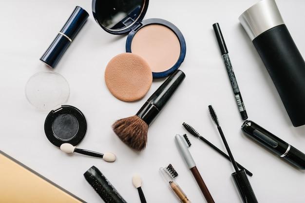 Różne zestawy kosmetyków do makijażu: pędzle, cienie do powiek, puder, tusz do rzęs, kosmetyki na jasnobiałej powierzchni