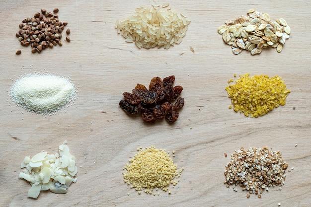 Różne ziarna owsianki zbożowej ustawione na drewnianym tle: gryka, ryż, kasza manna, pszenica, kuskus, płatki owsiane