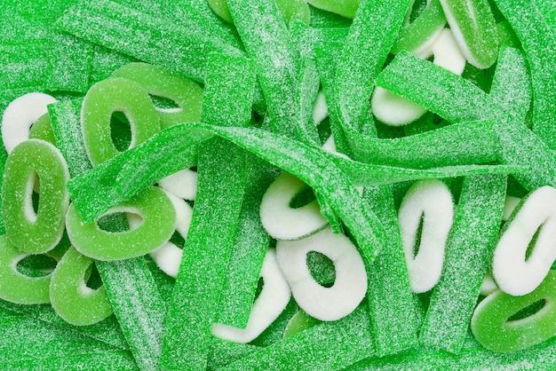 Różne zielone gumowate cukierki tło. widok z góry. słodycze galaretkowe.