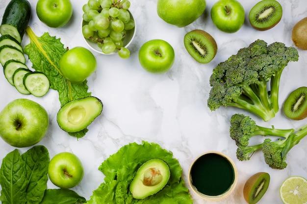 Różne zielone owoce i warzywa na marmurze