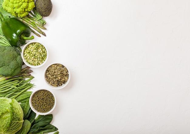 Różne zielone stonowane surowe organiczne warzywa. awokado, kapusta, brokuły, kalafior i ogórek z fasolką mung i mung, pak choi, papryką i sałatą