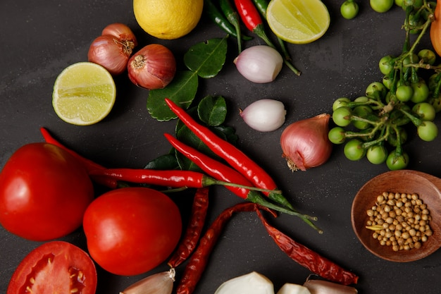Różne zioła i składniki do gotowania na ciemnym tle.