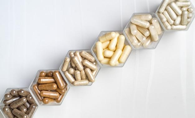 Różne ziołowe i homeopatyczne kapsułki medyczne w sześciokątnych słoikach w kształcie plastra miodu