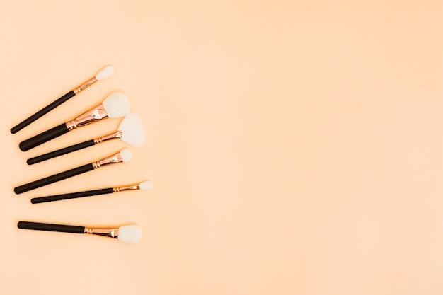 Różnego rodzaju pędzle do makijażu na beżowym tle