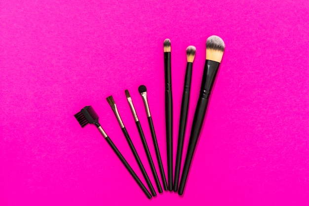 Różnego rodzaju pędzle do makijażu na różowym tle