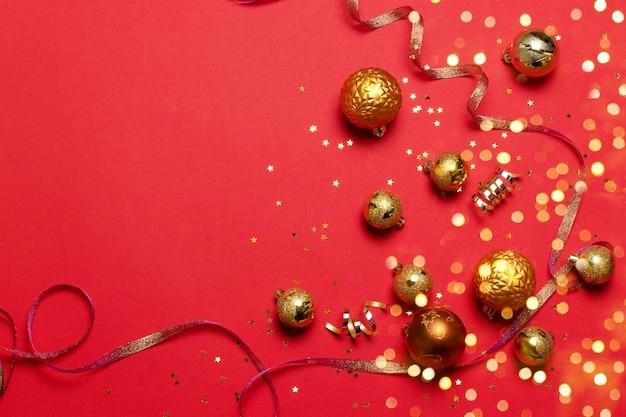 Różnej wielkości bombki złotego koloru z konfetti z brokatowymi gwiazdkami, satynowa błyszcząca wstążka na czerwonym gładkim tle. minimalistyczny pomysł na nowy rok lub święta bożego narodzenia.