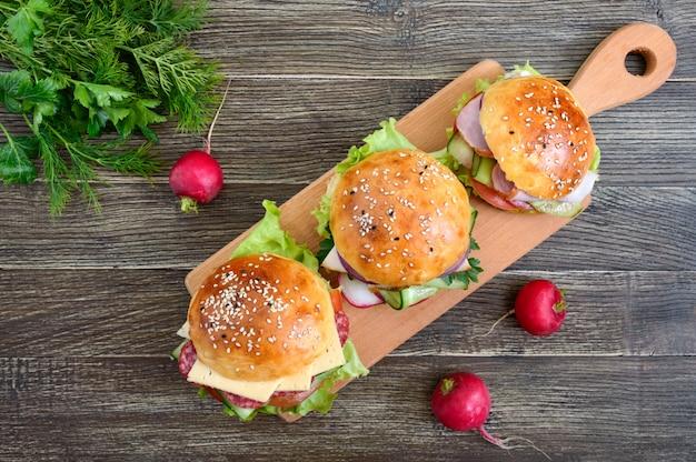 Różni hamburgery na drewnianej desce. domowa bułka z szynką lub mięsem lub salami, warzywami, ziołami. kanapki na lunch. widok z góry