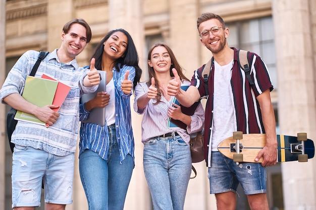 Różni koledzy-studenci szczęśliwie pokazują jak symbol