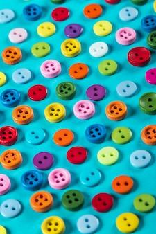 Różni kolorów guziki na błękitnym tle