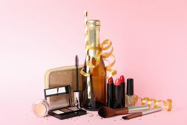 Różni kosmetyki do makijażu i szampan na różowym tle. akcesoria dla kobiet