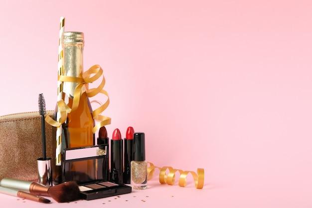 Różni kosmetyki do makijażu i szampan na różowym tle