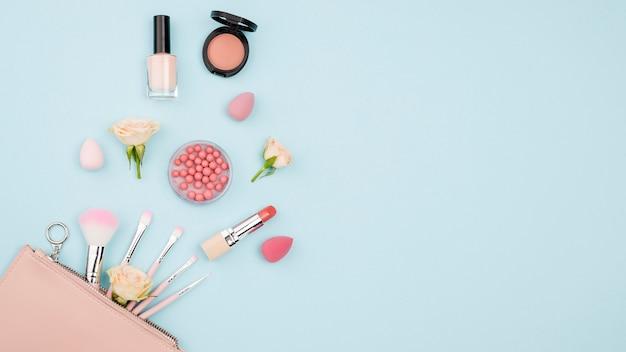 Różni kosmetyki z kopii przestrzenią na błękitnym tle