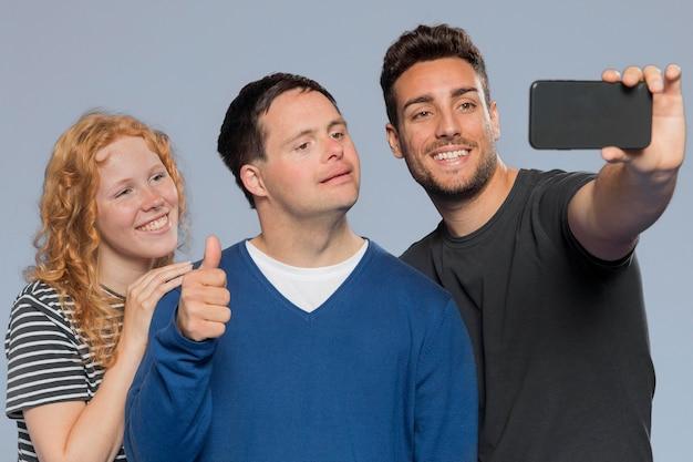Różni ludzie biorący selfie razem