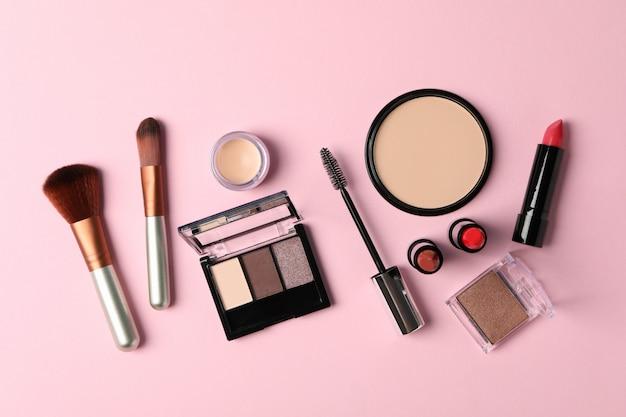 Różni makeup kosmetyki na różowym tle. akcesoria dla kobiet