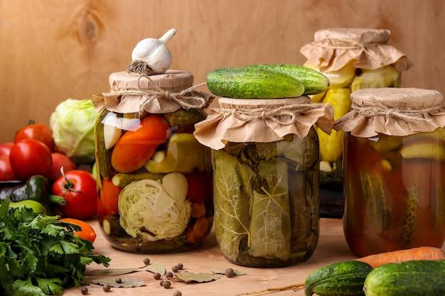 Różni marynowani warzywa w słojach na drewnianym stole