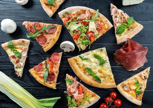 Różni plasterki pizza na ciemnym drewnianym tle. kuchnia włoska. tło zdjęcie żywności. jedzenie leżało płasko