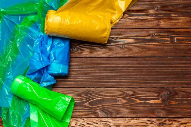 Różni plastikowi worki na drewnianym tle
