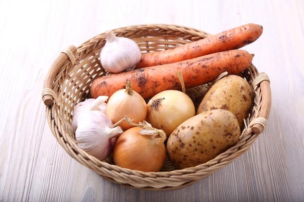 Różni warzywa w koszu na drewnianym stole
