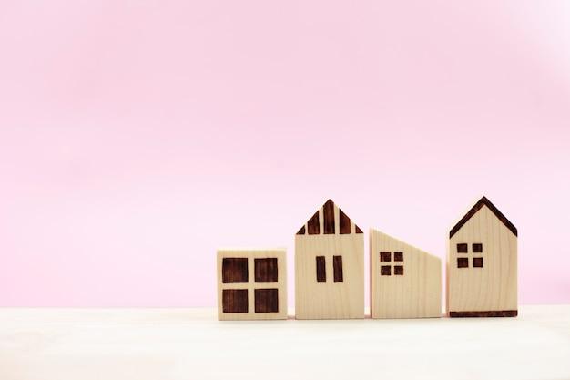 Różnicowy model domu na pastelowym różowym tle